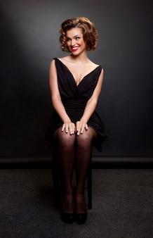 매력적인 헤어 스타일과 저녁 화장을 가진 여자, 검은 드레스를 입고 의자에 앉아