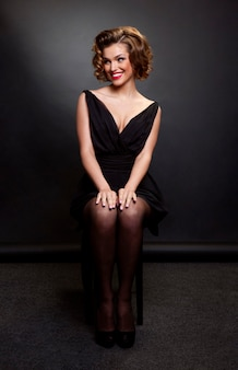 Woman with charming hairstyle and evening makeup, wearing black dress and seated on chair