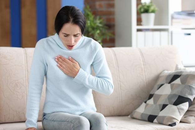 가슴 통증이 있는 여자가 소파에 앉아 있습니다. 심장 고통스러운 공격 개념