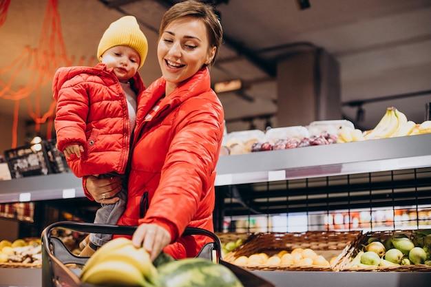 Donna con bambino in drogheria che compra prodotti