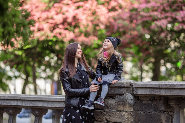 A woman with a child in her arms near the flowering tree. portrait of mother and daughter near a flowering tree