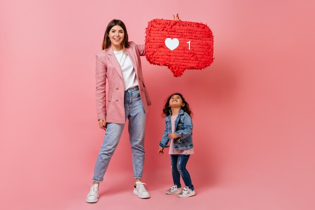 Woman with child holding social network icon. studio shot of mother and kid posing with like symbol.