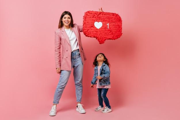 ソーシャルネットワークのアイコンを保持している子供を持つ女性。シンボルのようなポーズをとる母と子のスタジオショット。