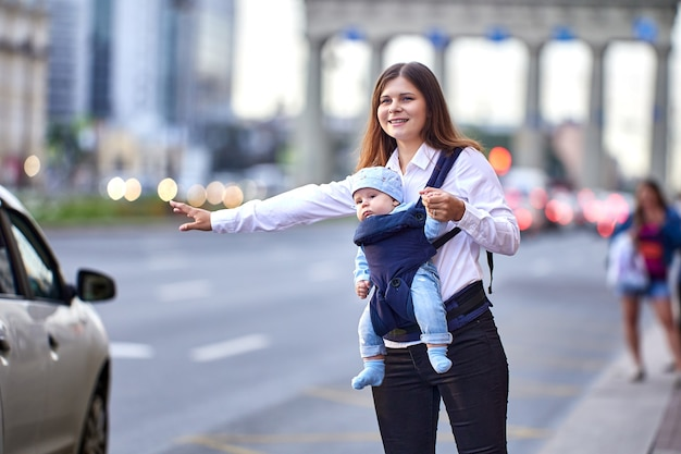 Женщина с ребенком в слинге останавливает такси на оживленной улице города