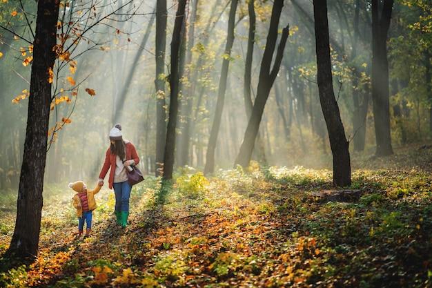 壁に子供を持つ女性。周りの素晴らしい秋の森