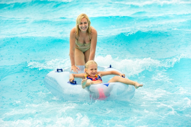 A woman with a child in a rubber inflatable circle plays in the pool of a summer water park in the rain