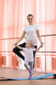A woman with a child standing doing yoga.