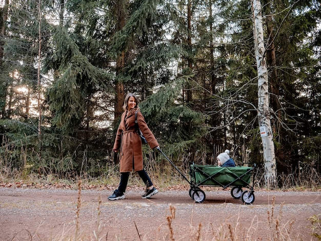 Woman with a child in a wagon walking down in the forest