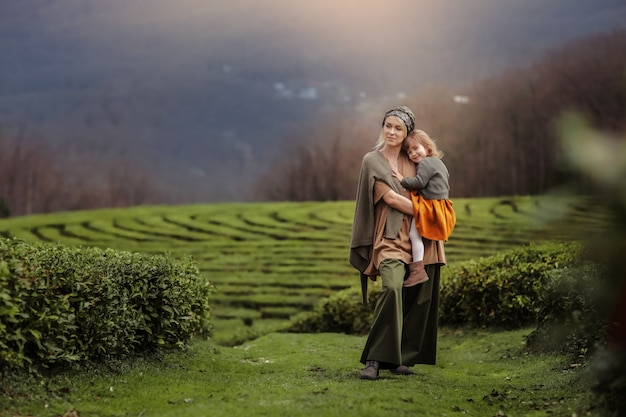A woman with a child walking on a tea plantation