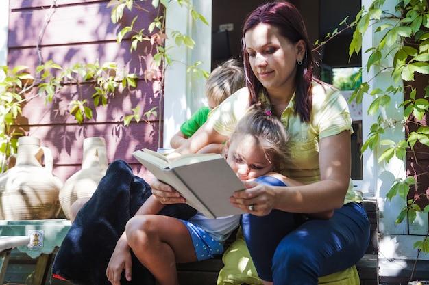 ポーチを読んでいる子供たちのいる女性