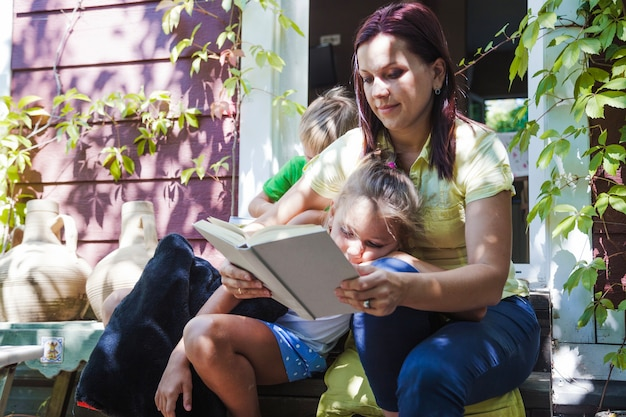 Woman with children reading on porch
