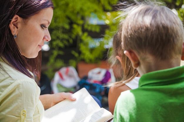 一緒に読んでいる子供たちのいる女性