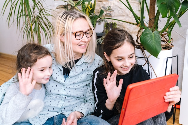 Woman with children sitting at home and holding videocall. family using smartphone for video call with friend or family. people communicates via video - looking camera and waving greeting hands