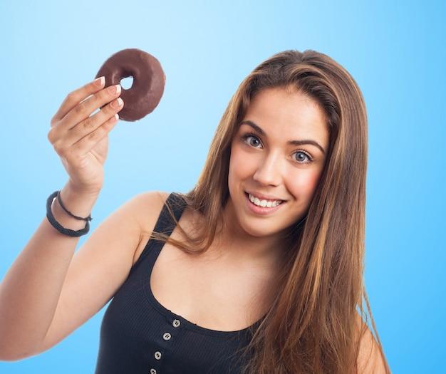 Donna con una ciambella al cioccolato in una mano