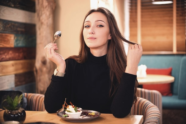 Woman with chocolate hair eating brownie cake dessert in cafe with great pleasure