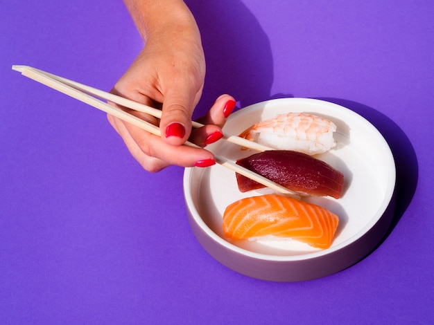 Woman with chopsticks taking a sushi from a white bowl