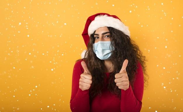 Женщина в новогодней шапке с оптимизмом смотрит на поражение коронавирусом covid 19 на желтом