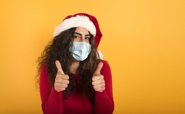 クリスマスの帽子をかぶった女性は、covid19コロナウイルスの敗北について楽観的です。