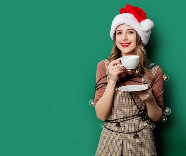 Woman with christmas lights and cup of coffee on green wall