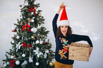 Woman with christmas present by christmas tree