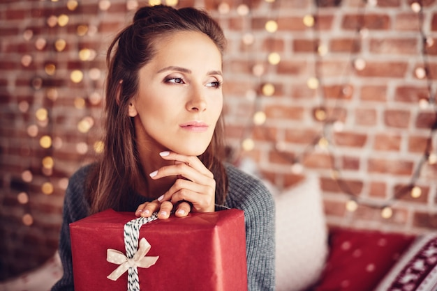 Женщина с рождественским подарком мечтает