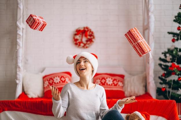 クリスマスツリーを提示するクリスマスを持つ女性