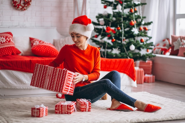 Woman with christmas presents by christmas tree