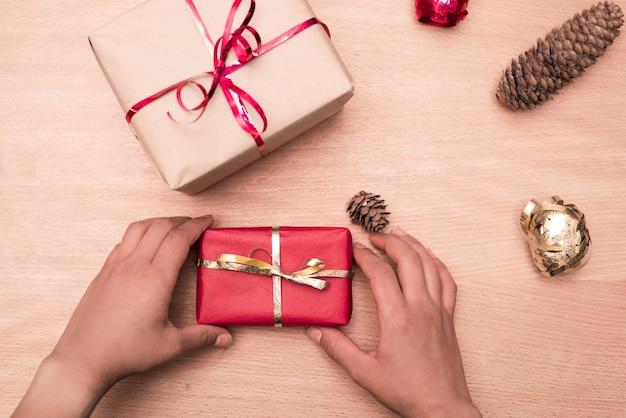 크리스마스 선물을 가진 여자는 나무 테이블에 배치