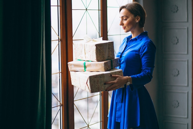 Woman with christmas presents standing by the window