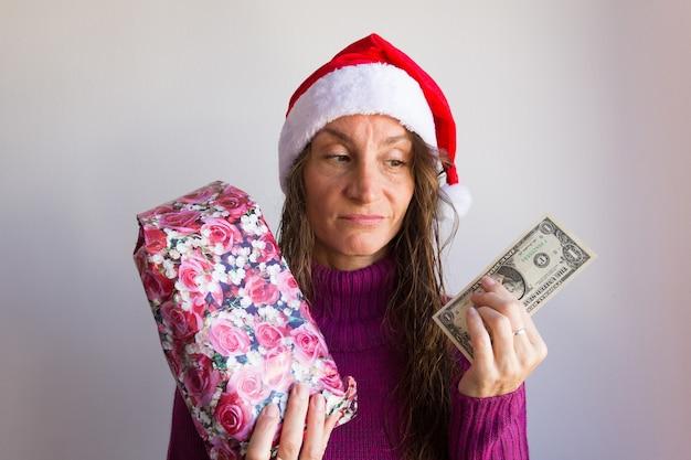 가난한 표정으로 포장된 선물과 달러 지폐를 들고 크리스마스 빨간 모자를 쓴 여자