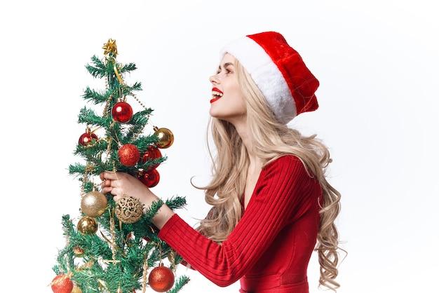 手にクリスマスツリーを持つ女性は、休日のクリスマスの装飾をおもちゃにします。高品質の写真