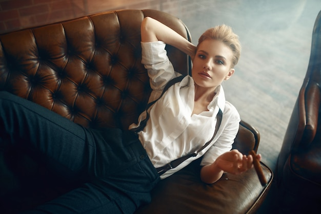 ソファに横になっている葉巻を持つ女性