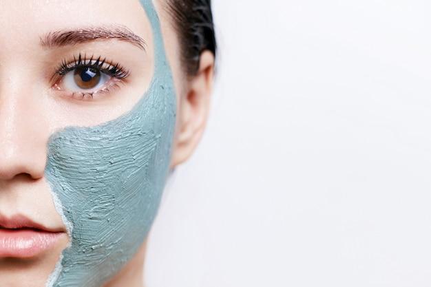 Женщина с глиняной маской для лица для ухода за кожей