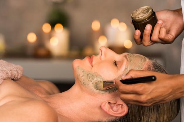 Женщина с глиняной маской на лице