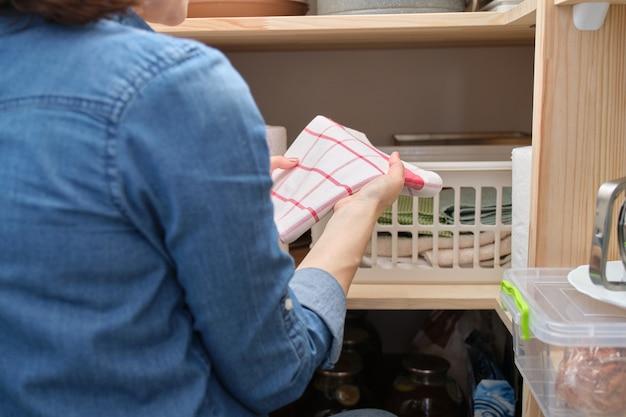 식료품 저장실에서 깨끗한면 주방 수건을 가진 여자