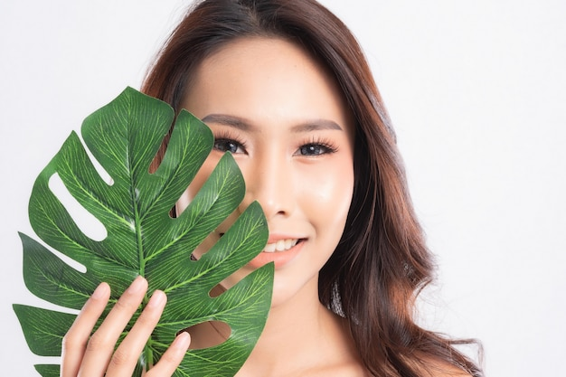 Woman with clean fresh skin holding green leaves. proposing a product. gestures for advertisement isolated on white.