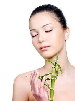 植物を保持している顔にきれいな肌を持つ女性