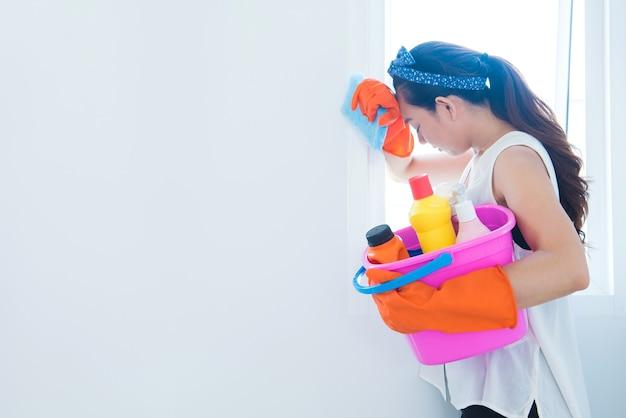 掃除用品と洗剤を持っている女性。一人で家を掃除するのに疲れた