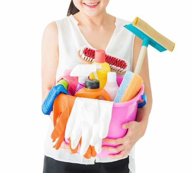 パスで家を掃除するための白い背景の上のクリーニング用品と洗剤を持つ女性