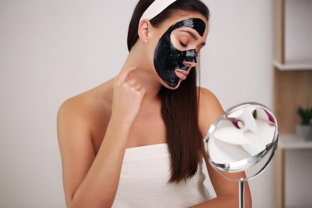 彼女の顔に黒いマスクをクレンジングを持つ女性