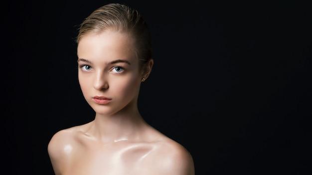 Женщина с ясным лицом и чистой кожей на черной стене