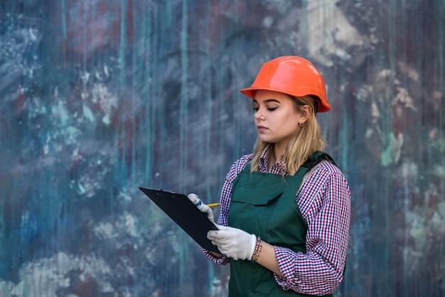 制服を着たクリップボードを持った女性が家の修理をします。リノベーションのコンセプト