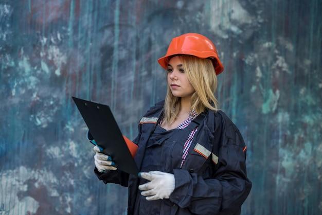 制服を着たクリップボードを持った女性が家で修理をします。リノベーションのコンセプト