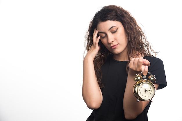 Donna con orologio che tiene la sua testa su sfondo bianco. foto di alta qualità