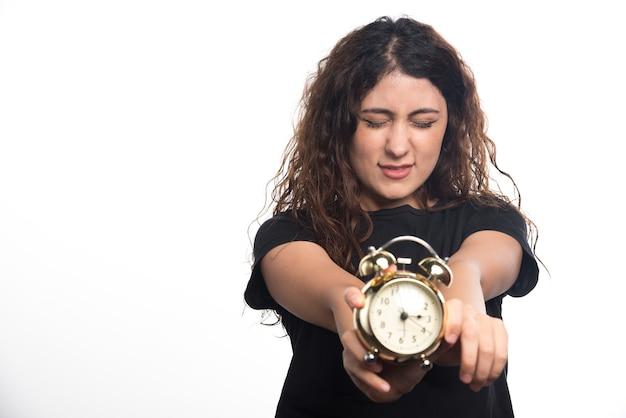 白い背景の上の目覚まし時計を示す目を閉じて女性