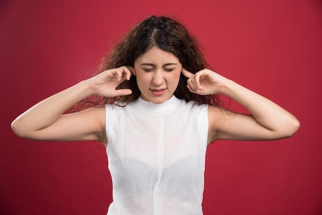 Женщина с закрытыми ушами на красном