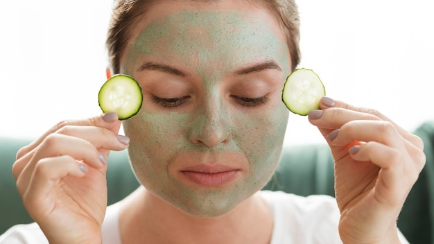 Woman with closed eyes applying slices of cucumber