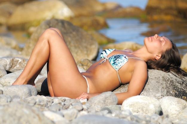 目を閉じて、腕を上げて頭の近くで、海岸の石の上に座っている水着の女性