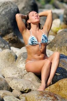 目を閉じて、腕を上げて、海岸の石の上に座っている水着で、頭の近くの女性