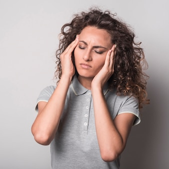 Woman with closed eyes having headache against gray background